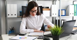 Documentos de relleno de la empresaria y trabajo en el ordenador portátil en oficina moderna metrajes