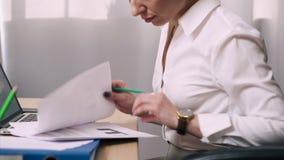 Documentos de visión femeninos del oficinista en lugar de trabajo