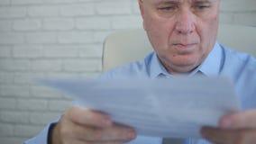 Documentos financeiros de Image Working With do homem de negócios no escritório fotografia de stock