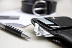 Documentos, pena, correia e uma carteira de couro em uma mesa de madeira foto de stock