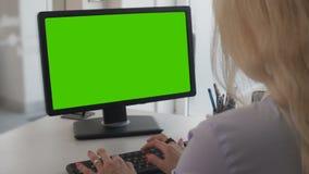 Documentos que mecanografían femeninos del oficinista en de computadora personal con la pantalla verde metrajes
