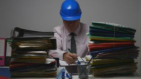 Documentos técnicos de Wearing Helmet Sign do coordenador na sala do arquivo imagem de stock