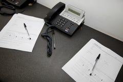 Documentos y teléfonos de la línea horizonte en la tabla Imágenes de archivo libres de regalías