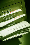Documents bulging out of a filling cabinet Royalty Free Stock Images