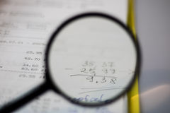 Documents, calculations and calculations by magnifying glass. On a white background Stock Photography