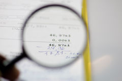 Documents, calculations and calculations by magnifying glass. On a white background Stock Photos