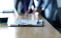 Documents with chart and graph and pen. On background of two employees working Stock Photos