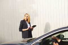 Documents checking by the woman employee, near the black car stock image