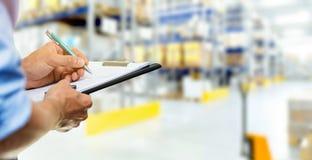 Documents d'écriture d'homme de service de logistique sur le presse-papiers dans warehous image stock