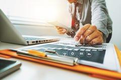 Documents d'entreprise sur le bureau avec l'ordinateur portable et le téléphone et le graphique futés photo stock