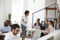Documents de présentation de femme aux collègues à un bureau dans le bureau photos stock