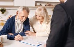Documents de signature de couples pluss âgé mignons avec du charme à la maison Photo libre de droits