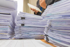 Documents on desk stack up high waiting to be managed. Royalty Free Stock Images