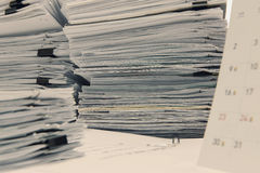 Documents on desk stack up high waiting to be managed Stock Photography