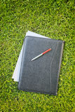 Documents in a Leather Folder over Green Grass Royalty Free Stock Images