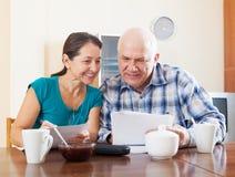 Documents mûrs de sourire de lecture de couples pendant le thé Image stock