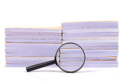 Documents and magnifier. On white background Stock Photos