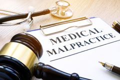 Documents about medical malpractice and gavel. Clipboard with documents about medical malpractice and gavel royalty free stock photos