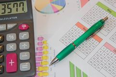 The documents painted colorful graphics. Above lies the pen and calculator royalty free stock images