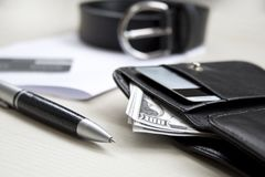 Documents, pen, belt and a leather wallet on a wooden desk. stock photo