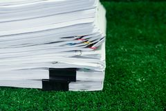 Documents pile on grass in concept save Earth. Use paper resources economically Royalty Free Stock Photos