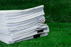 Documents pile on grass in concept save Earth and use paper econ. Omically and cost-effectively Royalty Free Stock Images