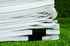 Documents pile on grass in concept save Earth. And use paper economically and cost-effectively royalty free stock image