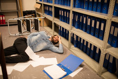 Documents scattered by fallen businessman in file storage room Stock Images