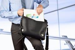 Documents se tenants et sortants d'homme d'affaires avec des graphiques de Photographie stock