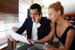 Documents sur papier de observation d'entrepreneur asiatique d'homme pendant la conversation de téléphone portable tandis que son Photographie stock libre de droits