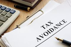 Documents about tax avoidance on a desk. Documents about tax avoidance on the desk stock image