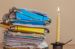 Documents to be read  in the light of a candle. Analyze a stack of documents and folders un the light of  a candle Royalty Free Stock Images