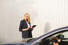 Documents vérifiant par l'employée, près de la voiture noire image stock