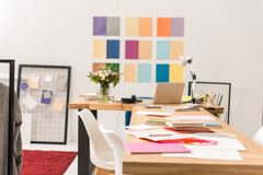 Documents at workplace in fashionable modern office with color palette. On wall royalty free stock image