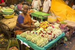 Documetary redaktörs- bild Oidentifierad mankvinnaförsäljning som skapar rep av blommor på den utomhus- huvudsakliga marknaden i  royaltyfri bild