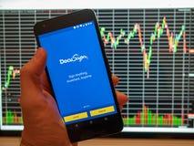 DocuSign κινητό app που κρατιέται μπροστά από ένα διάγραμμα δείκτη μετοχής σε έναν ομο Στοκ φωτογραφία με δικαίωμα ελεύθερης χρήσης