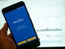DocuSign κινητό app που κρατιέται μπροστά από ένα φωτεινό διάγραμμα δείκτη μετοχής Στοκ φωτογραφίες με δικαίωμα ελεύθερης χρήσης