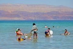 Dode overzees, Israël - 31 MEI 2017: de mensen op stoelen ontspannen en zwemmen in het water van het Dode Overzees in Israël Toer royalty-vrije stock foto's