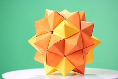 Dodecahedron origami on green background. Beautiful 3D paper model as item of exposition. Child`s talent and creativity Royalty Free Stock Photos