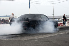 Dodge challenger hellcat smoke show. Rear side view of black dodge challenger making a smoke show at the starting line on the track during the festidrag event at royalty free stock images