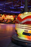 Dodgem Car. Rear end of a dodgem car at the fair. Close up detail with soft focus neon lights of the fair in the background Stock Image