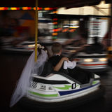 Dodgem Wedding. A bride and groom get fired up in a dodgem car on their wedding day Stock Photos