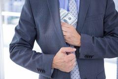 Dodgy businessman with dollar bills Stock Image