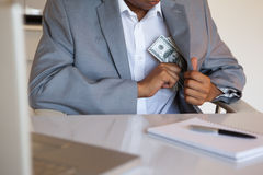 Dodgy businessman pocketing wad of dollars Stock Photography