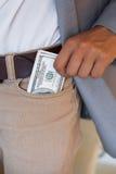 Dodgy businessman pocketing wad of dollars Royalty Free Stock Photography