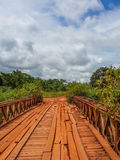 Dodgy wooden bridge with timber planks and old iron rails crossing river in Gabon, Central Africa Stock Images