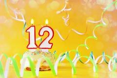 Dodici anni di compleanno Bigné con le candele brucianti sotto forma di numero 12 fotografia stock libera da diritti