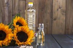 Dodsolnechnoe-Öl in einer Flasche von einem großen und ein klein, in einem Blumenstrauß von Sonnenblumenblumen, auf einem kleinen stockbild