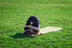 Doeing asans Yoga der jungen schönen Sitzfrau auf dem grünen Gras mit Yogamatte Lizenzfreie Stockfotografie