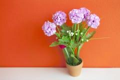Doekbloemen, kunstmatige decoratie op oranje muur Stock Foto